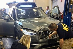 US National Transportation Safety Board (NTSB) investigators examine a self-driving Uber vehicle involved in a fatal accident in Tempe, Arizona, on March 20, 2018.