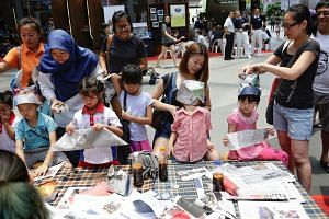 Children learning to make animal hats out of old newspapers at the Just-One-Earth Carnival at Our Tampines Hub on March 24, 2018.