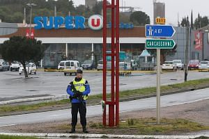 Above: Lieutenant-Colonel Arnaud Beltrame, who once served in Iraq, was rushed to hospital after being shot three times by the Islamist militant but died later. Right: A French gendarme outside the Super U store in the southwestern town of Trebes yes