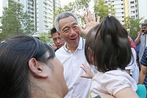Prime Minister Lee Hsien Loong greeting a baby and her mother at the Kids and Babies Carnival in Sengkang South yesterday. The new facilities were planned after collecting feedback from residents.