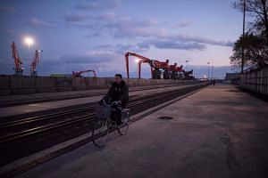 A man cycles past the railway at the joint Russian-North Korean RasonConTrans coal port in Rason, North Korea. Russia said it is planning to build a second bridge to North Korea for future trading.