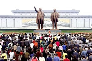 North Koreans laying floral tributes to the statues of North Korea founder Kim Il Sung and late leader Kim Jong Il in Pyongyang in a photo released on Oct 10, 2017.