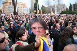 Protestors holding cardboard masks with the face of former Catalan leader Carles Puigdemont during a march in Tarragona, Catalonia, on March 25, 2018.
