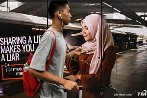 """An advertisement with the slogan """"sharing a lie makes you a liar"""" at a train station in downtown Kuala Lumpur on March 26, 2018."""