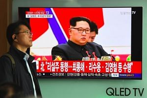 A man walks past a television screen showing a news report about a visit to China by North Korean leader Kim Jong Un, at a railway station in Seoul on March 28, 2018.