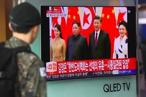 A South Korean soldier watches a news clip about a visit to China by North Korean leader Kim Jong Un, at a railway station in Seoul on March 28, 2018.