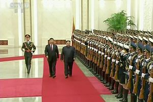 North Korean leader Kim Jong Un and Chinese President Xi Jinping inspect honour guards during a welcoming ceremony in China, in this still image taken from video released on March 28, 2018.