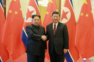 North Korean leader Kim Jong Un (left) shakes hands with Chinese president Xi Jinping (right), as he paid an unofficial visit to China, on March 28, 2018.
