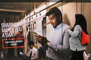 """An advertisement reading """"sharing a lie makes you a liar"""" at a train station in downtown Kuala Lumpur on March 26, 2018."""