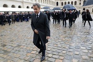 Former French President Nicolas Sarkozy leaves after a national ceremony for late Lieutenant-Colonel Arnaud Beltrame at the Hotel des Invalides in Paris on March 28, 2018.