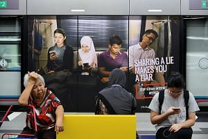 Commuters in front of an advertisement discouraging the dissemination of fake news, at a train station in Kuala Lumpur. The proposed law penalises those who maliciously create or spread such content.