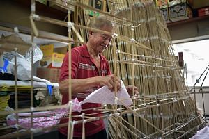 Mr Tan Ah Hock assembling the paper houses, which are used as offerings for the dead, by hand. It is a craft he picked up from his father, who in turn learnt it from his own father. The number of storeys these houses have depends on the dead person's