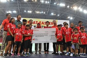 Great Eastern group CEO Khor Hock Seng presenting a cheque for $169,085 to Mr Gerard Ee, a member of the Board of Trustees for Straits Times School Pocket Money Fund, at the National Stadium on March 31, 2018. With them are President Halimah Yacob an