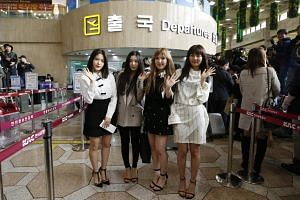 Members of South Korean pop group Red Velvet pose for photos at Incheon Airport, before departing for North Korea.
