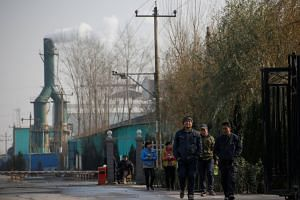 Smoke billows from a chimney as workers leave a factory in Hebei province, China.