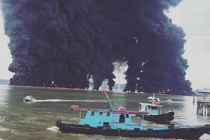 Thick plumes of smoke rise from fires near Balikpapan, Indonesia, on March 31, 2018, following an oil spill.