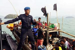 A Malaysian Maritime Enforcement Agency officer on the boat carrying Rohingya refugees, after it was intercepted off Langkawi yesterday. The coast guard said there were 19 men, 17 women, 12 girls and eight boys on the boat. The vessel was first seen