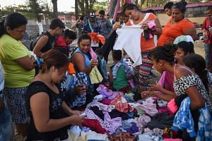 Central American migrants taking part in the caravan towards the US check out donated clothes in Mexico, on April 4, 2018.