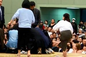 Women climbing up a sumo ring to treat Maizuru city mayor Ryozo Tatami, who collapsed while making a speech in a gym in Maizuru, Japan on April 4, 2018.