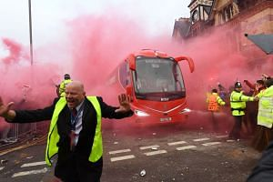 Police hold back supporters as Liverpool players arrive by bus at the stadium.