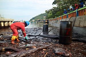 An Indonesian worker from state owned oil company, Pertamina, cleaning up oil on Melawai beach after an oil spill in Balikpapan, East Kalimantan, Indonesia, on April 4, 2018.