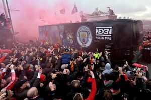 Liverpool supporters ignite red flares as the Manchester City team bus arrives prior to the UEFA Champions League quarter final first leg match on April 4, 2018.