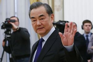 Wang Yi waves during a meeting with Russia's President Vladimir Putin at the Kremlin in Moscow.