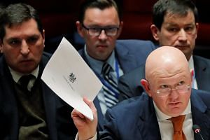 Russian Ambassador to the United Nations (UN) Vasily Nebenzya holds a copy of a British report on an incident in Salisbury, UK, during a meeting of the UN Security Council, on April 5, 2018.