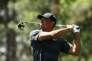Woods plays an approach shot on the ninth hole during the first round.