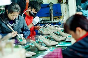 Workers producing shoes for export at a factory in Shangrao, in China's central Jiangxi province.