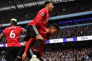 Smalling (right) celebrates scoring his team's third goal with team mate Jesse Lingard.