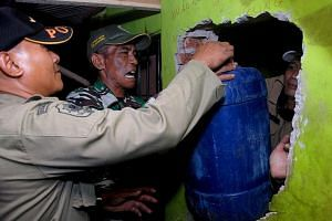 Indonesian police remove a container filled with illegal alcohol from a house in Cicalengka district in West Java province on April 8, 2018.