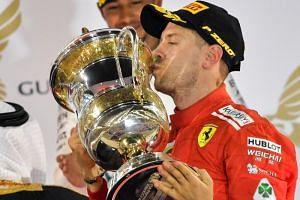 Ferrari's German driver Sebastian Vettel kisses his trophy after winning the Bahrain Formula One Grand Prix at the Sakhir circuit in Manama on April 8, 2018.