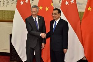 Singapore's Prime Minister Lee Hsien Loong shakes hands with Chinese Premier Li Keqiang before their meeting at the Diaoyutai State Guesthouse in Beijing, China, on April 8, 2018.