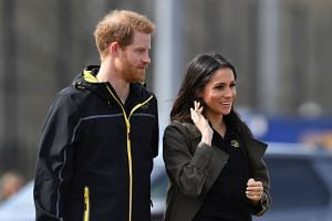 Britain's Prince Harry (left) and his fiancee Meghan Markle arrive to meet participants at the UK team trials for the Invictus Games Sydney 2018, on April 6, 2018.