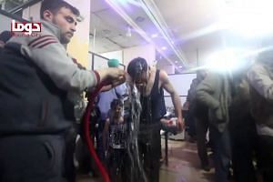 Unidentified volunteers spraying a man with water at a make-shift hospital following an alleged chemical attack on the rebel-held town of Douma on April 7, 2018.
