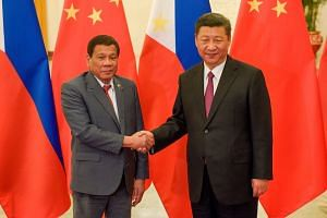 A file photo of Chinese President Xi Jinping (right) shaking hands with Philippines President Rodrigo Duterte prior to their bilateral meeting during the Belt and Road Forum, on May 15, 2017.