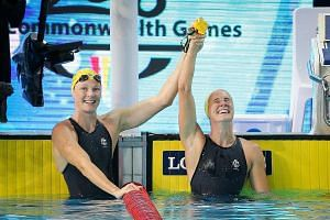 Bronte Campbell (right) is congratulated by her sister Cate after they finish first and second respectively in the 100m freestyle at the Optus Aquatic Centre on Monday. Bronte's gold was one of Australia's 28-medal haul at these Games.