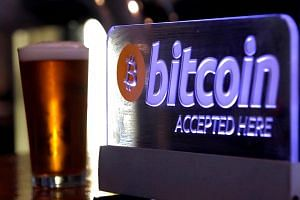 A Bitcoin sign on display at a bar in central Sydney, Australia. Effective immediately, all so-called digital currency exchange providers with operations in Australia must register with AUSTRAC, the government agency said in a statement.