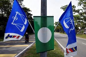 A motorcyclist is seen near flags of the ruling party Barisan Nasional and Parti Islam SeMalaysia in Bangi, Malaysia on April 10, 2018.