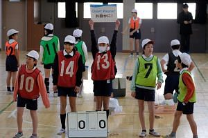 Blindfolded children playing goalball, a sport for the visually impaired, during a class at a school in suburban Tokyo.