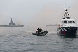 A Republic of Singapore Navy Littoral Mission Vessel (background, far left), and the Police Coast Guard's patrol interdiction boat (at right) intercepting a mock terrorists' speedboat in Singapore waters off Changi Coast Road during a demonstrati
