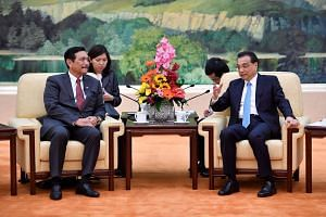 Indonesian Coordinating Maritime Affairs Minister Luhut Pandjaitan listens to Chinese Premier Li Keqiang (right) during their meeting at the Great Hall of the People in Beijing on April 12, 2018.