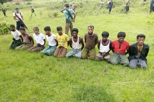 Rohingya Muslim men with their hands bound kneel as members of the Myanmar security forces stand guard in Inn Din village on Sept 2, 2017.