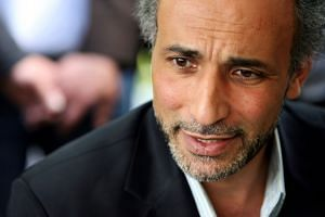 Tariq Ramadan talks with a journalist after a 2010 conference in Nantes, France.