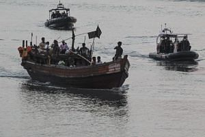 A boat carrying 56 Rohingya refugees from Myanmmar is escorted to Kuala Kedah jetty before being handed to authorities at the Kedah Immigration Department, in Kedah State, Malaysia, on April 3, 2018.
