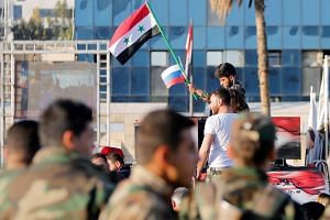 A Syrian soldier waves Russian and Syrian flags during a protest against air strikes in Damascus, Syria, on April 14, 2018.