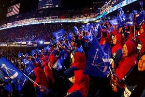 Members of the audience cheering at the arrival of Barisan Nasional's party chairman, PM Najib Razak.