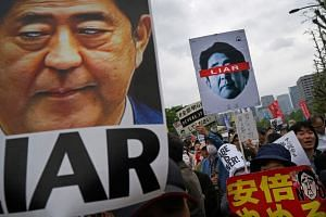 People protest against Japan's Prime Minister Shinzo Abe outside the National Diet building in Tokyo.