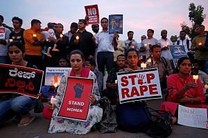 People protesting against the gang rape and murder of an eight-year-old girl in Jammu and Kashmir and the rape of a teenager in Uttar Pradesh at a candlelight vigil in Bengaluru, India, on Friday.
